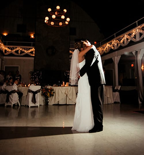 Couple having their first dance on dance floor with white light shining on them