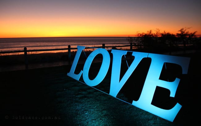 Love sign lit up with tiffany blue uplights at the Broome Surf Life Saving Club